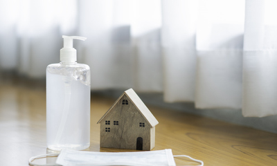 Hand sanitizer with protective mask next to small wooden model house
